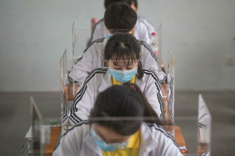 In China zitten jongeren achter plastic schermen en dragen ze een mondmasker in de klas.
