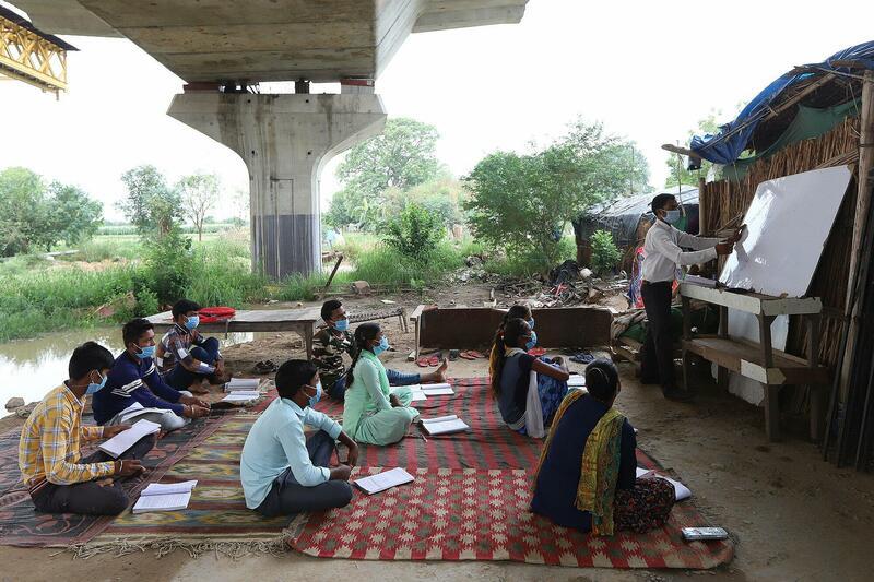 Een student geeft studenten uit kansarme milieus in New Delhi, India les omdat ze niet de kans hebben om online les te volgen.