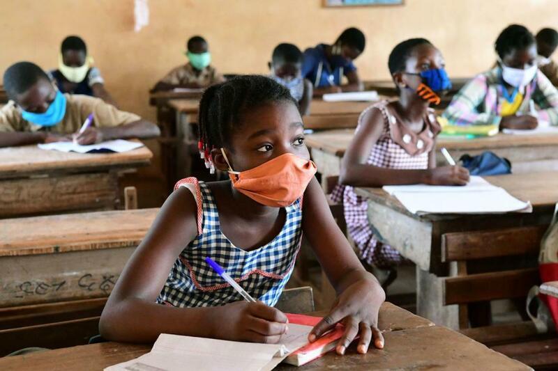 Leerlingen dragen kleurrijke mondmaskers en houden voldoende afstand van elkaar in Ivoorkust.