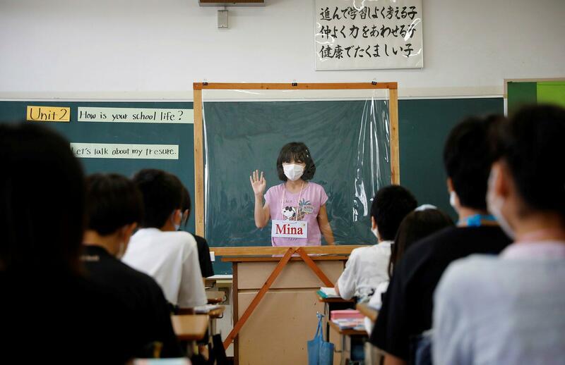Een Japanse studente geeft een presentatie achter een plastic scherm.