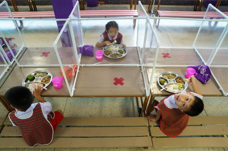 Kinderen zitten apart aan tafel tijdens de lunch in deze Thaise school.