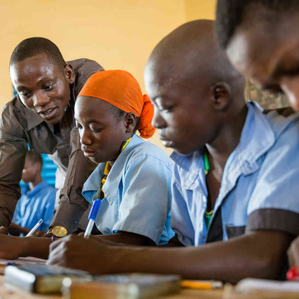 A teacher helps his students in class in Niger