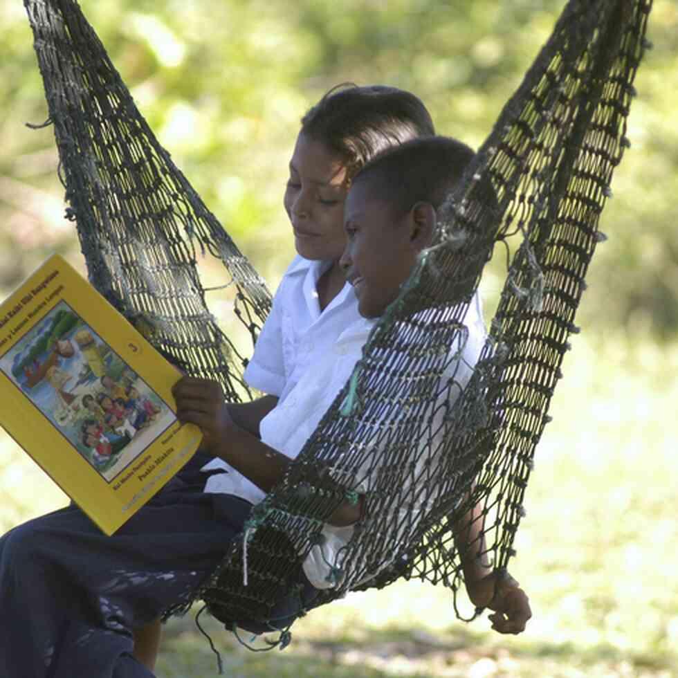 Children reading a book in a hammock.  Credit: GPE/Paul Martinez